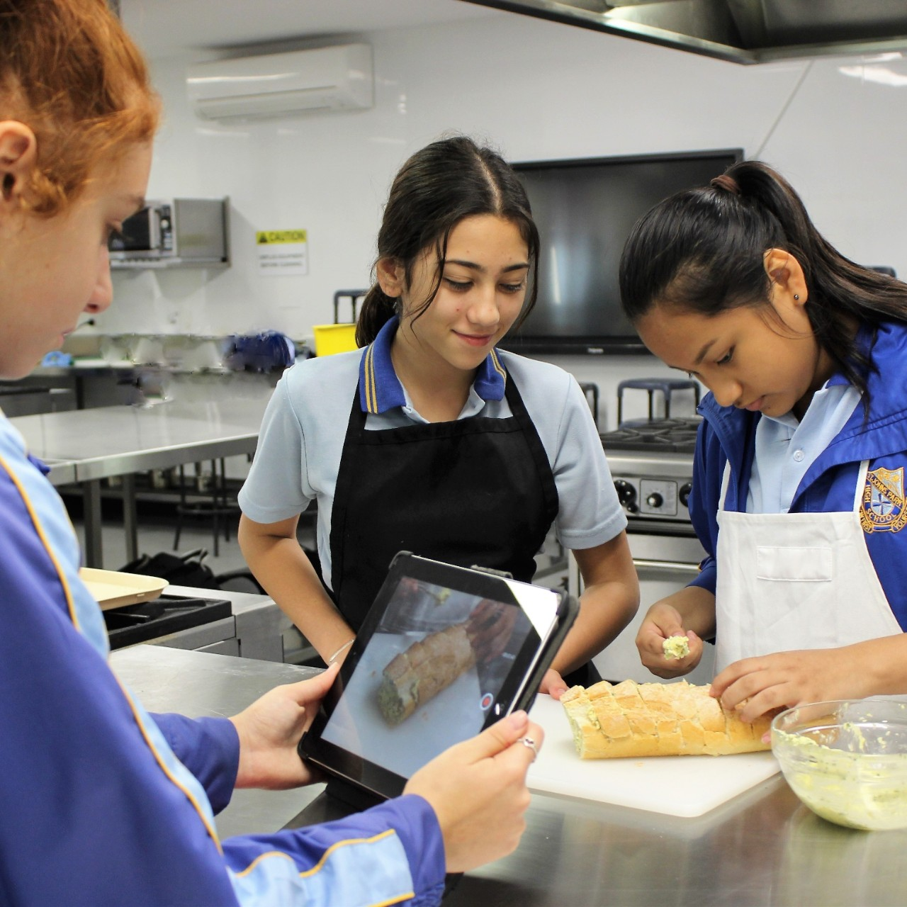 Students videoing cooking in commercial kitchen
