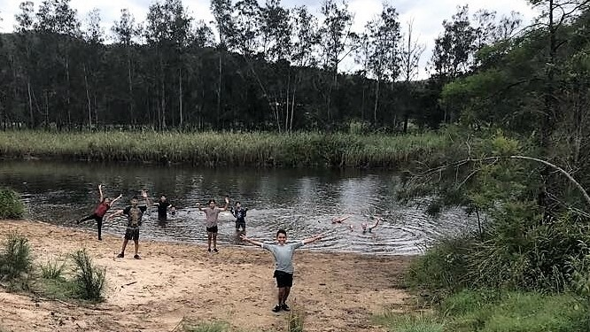 Students waving out of the lake